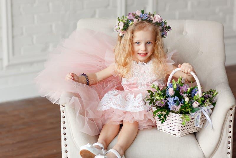 Stor stående av en gullig unge - flicka i a i en rosa klänning- och blommakrona Den härliga lilla flickan i en ljus studio sitter fotografering för bildbyråer