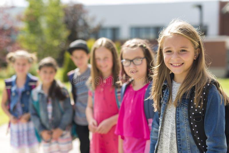 Stor stående av skolaeleven utanför bärande påsar för klassrum arkivbild