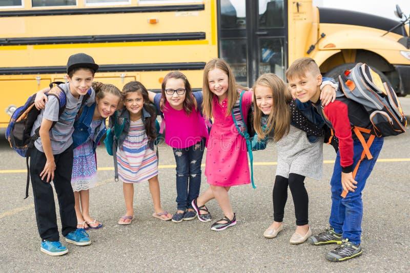 Stor stående av skolaeleven utanför bärande påsar för klassrum fotografering för bildbyråer