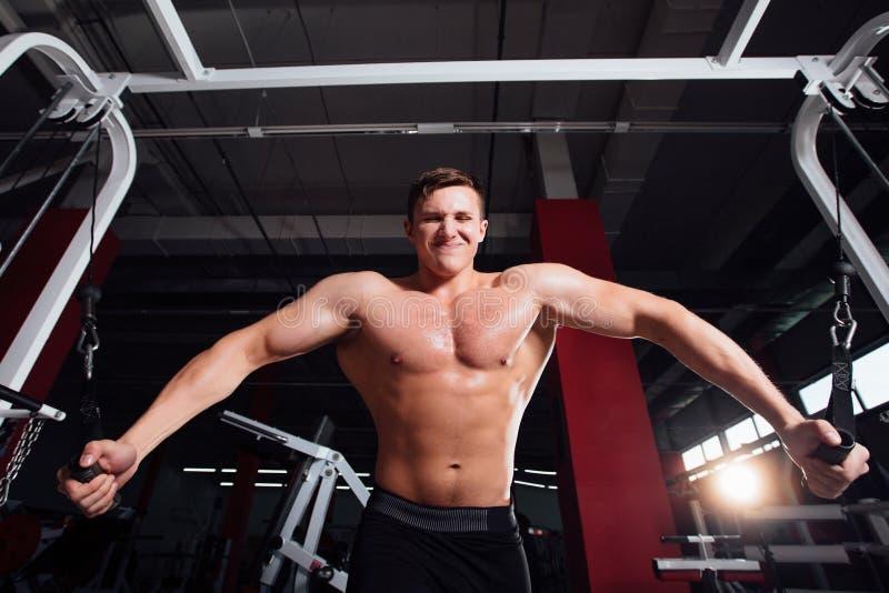 Stor stark bodybuider utan skjortor visar övergångsövningar De bröst- musklerna och den hårda utbildningen arkivbilder