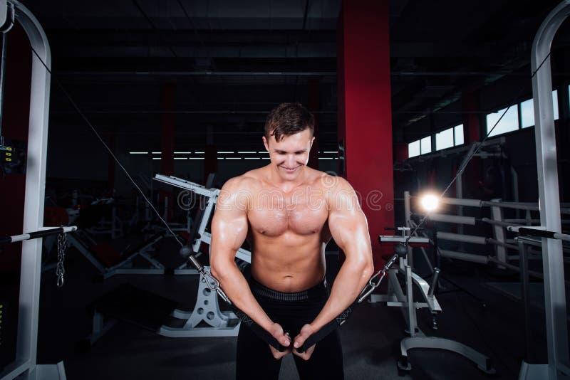 Stor stark bodybuider utan skjortor visar övergångsövningar De bröst- musklerna och den hårda utbildningen royaltyfri foto