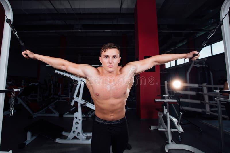 Stor stark bodybuider utan skjortor visar övergångsövningar De bröst- musklerna och den hårda utbildningen royaltyfri fotografi