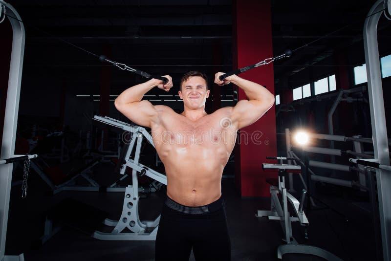 Stor stark bodybuider utan skjortor visar övergångsövningar De bröst- musklerna och den hårda utbildningen arkivfoto