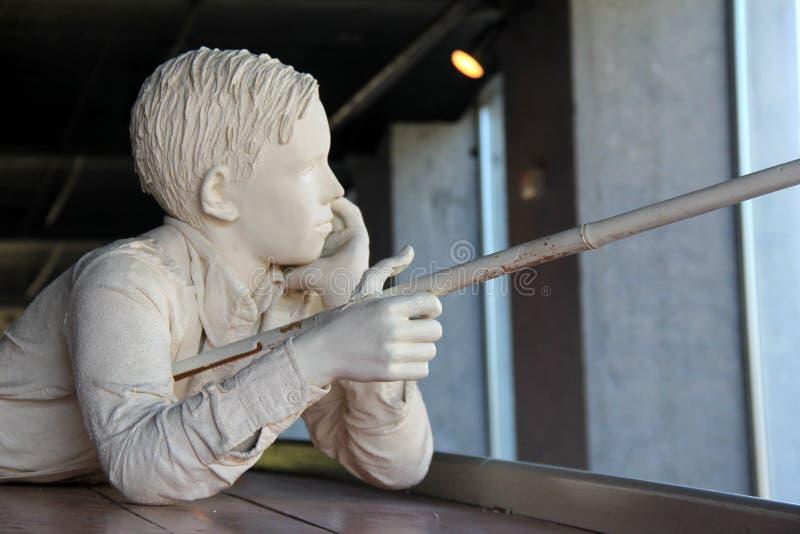 Stor staty av den unga pojken som fiskar av sida av kanalfartyget under liv längs den kusliga kanalen, Syracuse, New York, 2017 royaltyfri fotografi