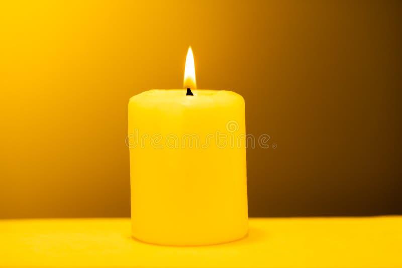Stor tänd stearinljus på en varm gul bakgrund arkivbilder