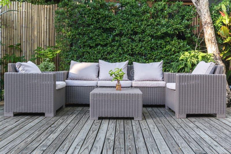 Stor terrassuteplats med rottingträdgårdmöblemang i trädgården på trägolv arkivfoto