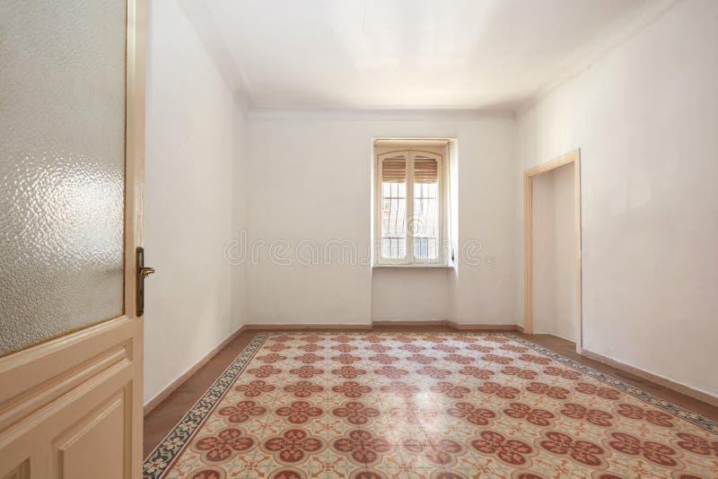 Stor tom ruminre med det gamla geometriska belade med tegel golvet arkivfoto