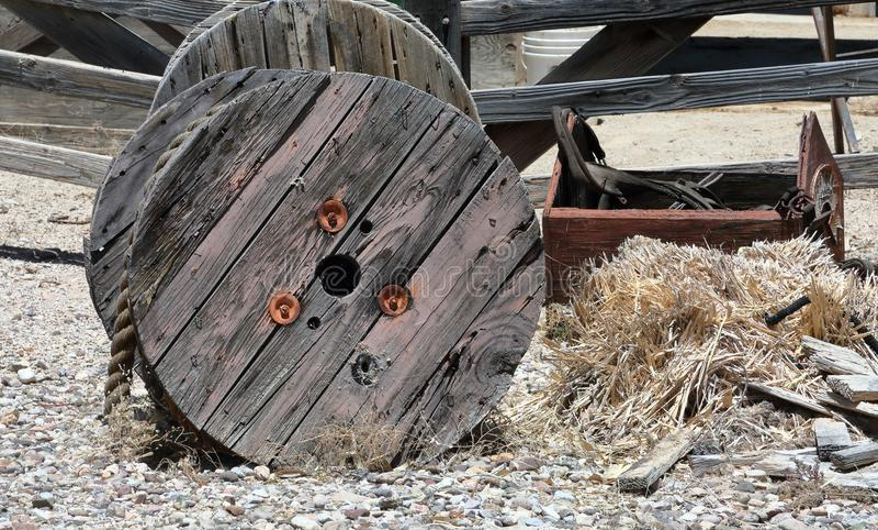 Stor trärulle med det tunga repet och en bruten toolbox på framdel av ett ridit ut staket royaltyfri fotografi