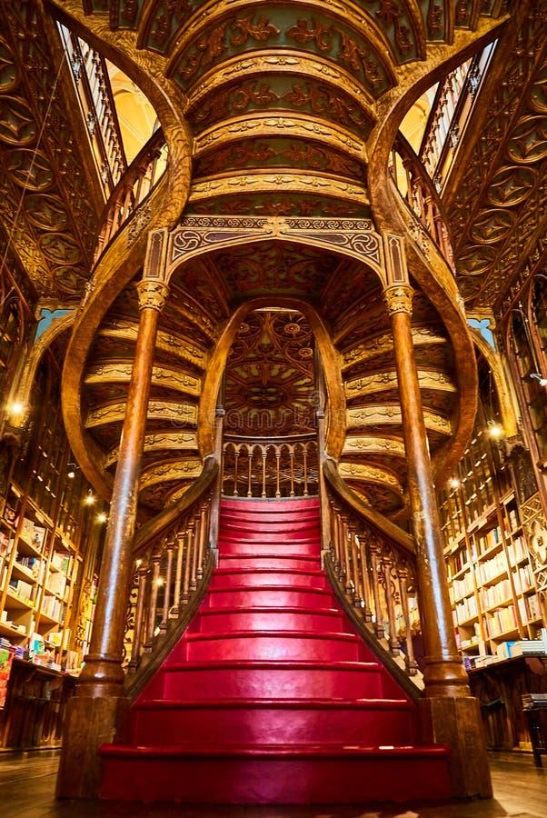 Stor trätrappuppgång med röda moment inom arkivbokhandeln Livraria Lello i den historiska mitten av Porto som är berömd för Harry arkivfoton