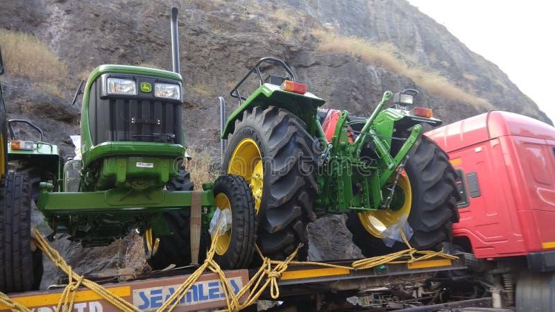 Stor traktor som klibbas på vägen, medan få transporterat till visningslokaler arkivbilder