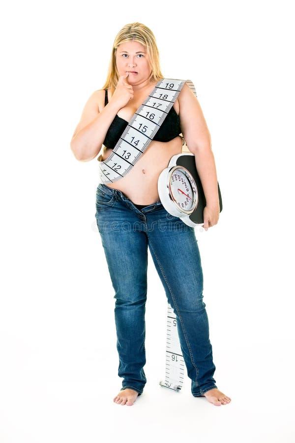 Stor ung kvinna med vägningsvåg under armen fotografering för bildbyråer