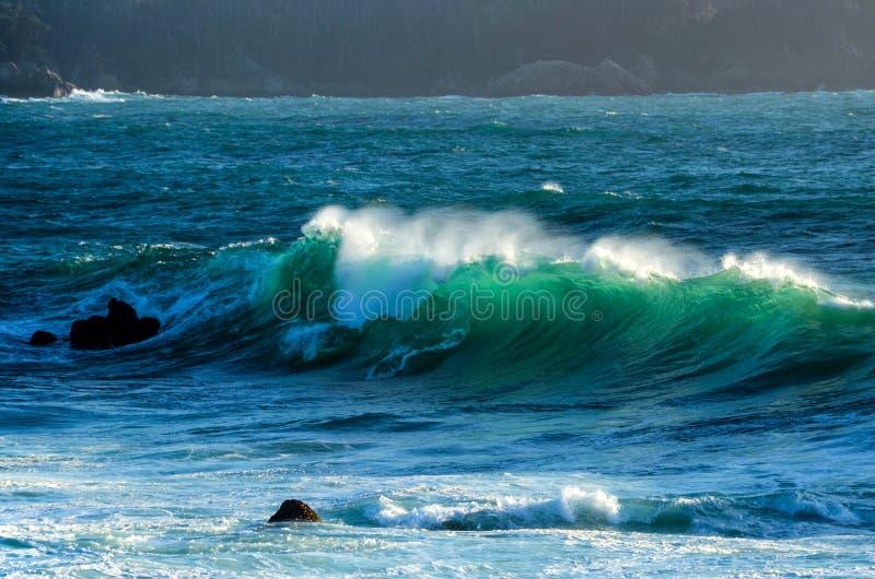Stor våg av blått vatten för klar aqua som är bakbelyst vid solen royaltyfria bilder