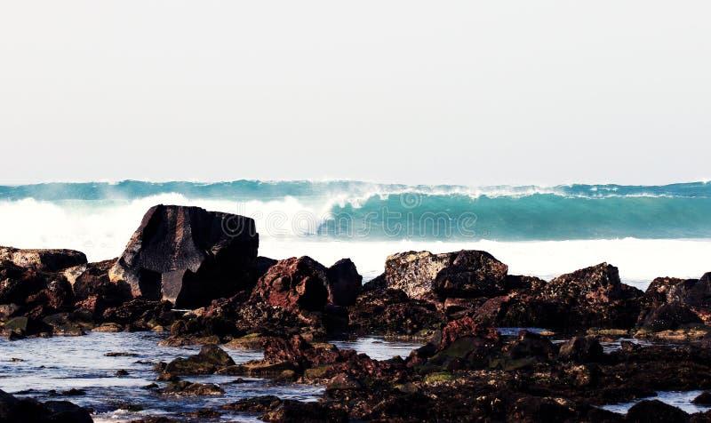 Stor våg på bakgrunden av stenar arkivfoton