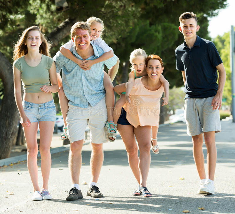 Stor vanlig familj som går med ungar på föräldrar tillbaka i summe royaltyfri fotografi