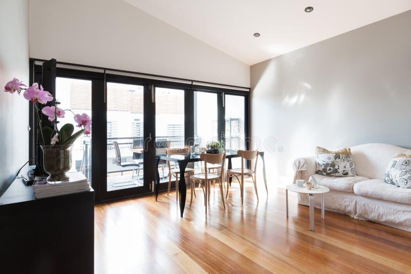 Stor vardagsrum för studiolägenhet med biveckdörrar royaltyfri bild