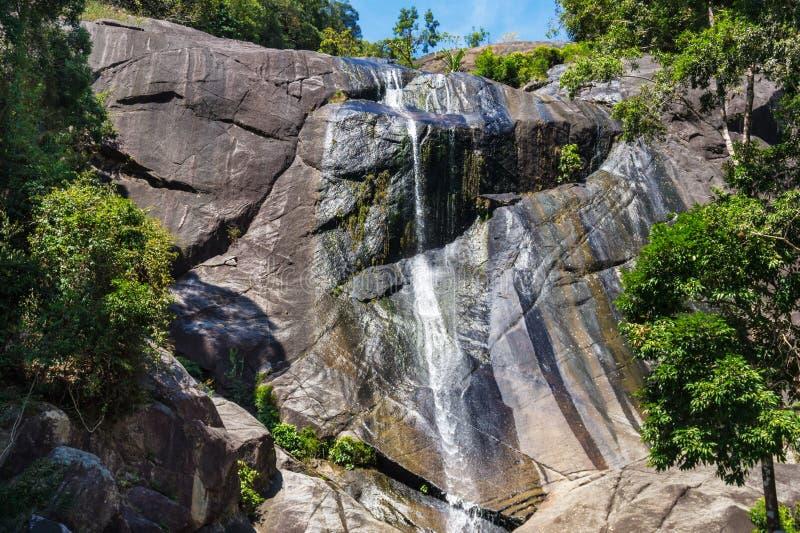 Stor vattenfall i steniga berg på den tropiska ön i Asien royaltyfria bilder
