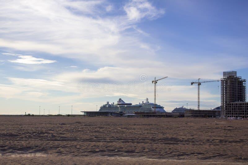 Stor vit kryssningeyeliner i den sandiga öknen nära tornkranarna som bygger moderna höghus royaltyfria foton