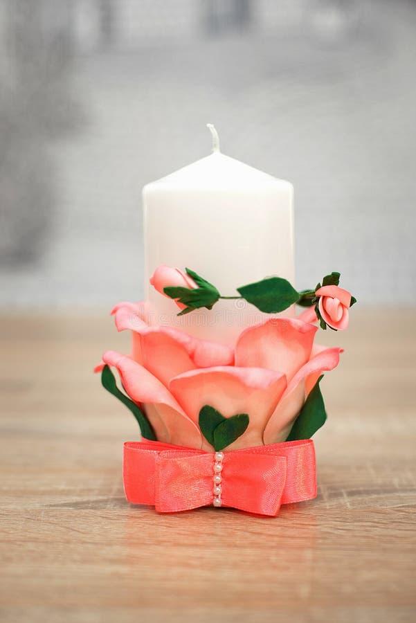 Stor vit stearinljus som dekoreras med rosor royaltyfria bilder