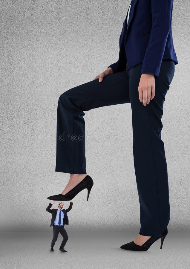 Stora affärerkvinna som försöker att kliva på en små och medelstora företagman royaltyfri bild