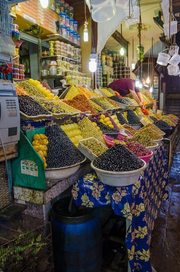 Stora belopp av pyramidically staplade oliv som är till salu på marknad eller soukh av Marrakesh, Marocko arkivfoton