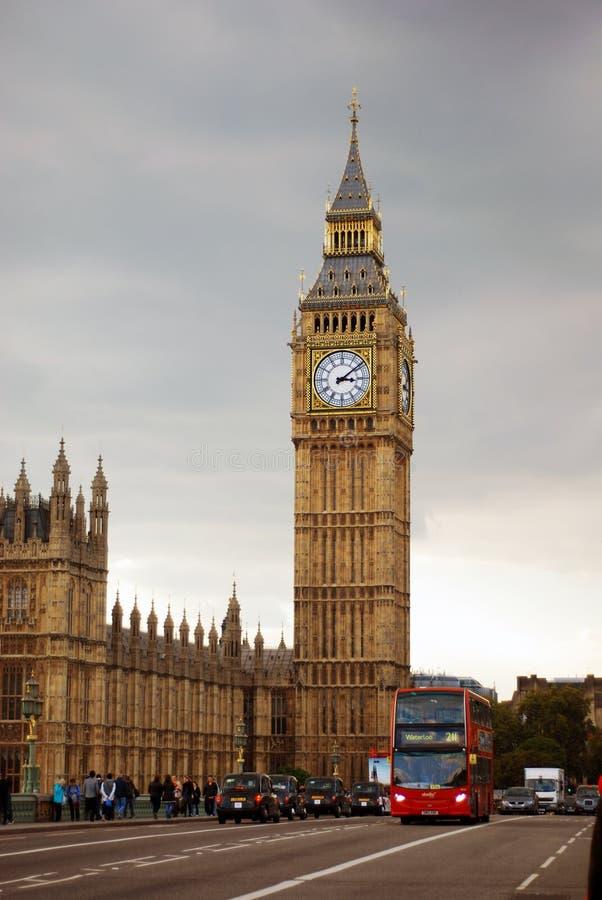 Stora Ben Tower Near City Road med bussen och bilar som reser under Gray White Clouds royaltyfria bilder