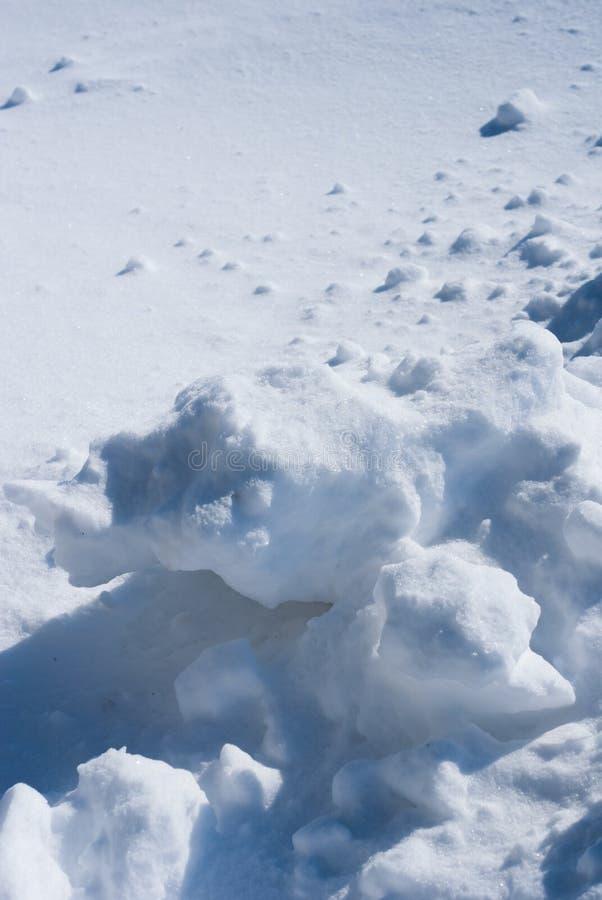Stora bitar av insnöad bakgrund av snö på en solig vinterdag arkivfoto