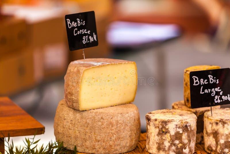 Stora bitar av olika ostar på en lokal fransk marknad arkivfoton