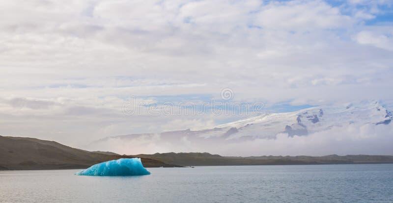 Stora bitar av is- is svävar i en lugna lagun royaltyfri fotografi