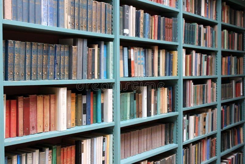 Stora blåa bokhyllor som fodras med gamla historiska romaner och bildande textböcker, Oneida Community Mansion House, Oneida, NY, fotografering för bildbyråer