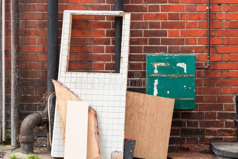 Stora bräden och avfallsobjekt som lämnas på hörnet av den London gatan arkivbilder