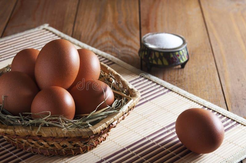 Stora bruna fega ägg ligger på sugrör i vide- korg och ett ägg nära på en trätabell arkivbild