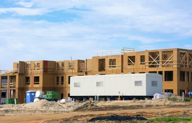 Stora byggarbetsplatser med husvagn för mobil arbetsförmedling på en solig morgon royaltyfri foto