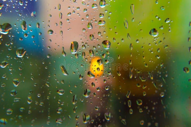 Stora droppar av regn på exponeringsglaset bak som en brinnande stearinljus och en suddig bakgrundsmakroskytte royaltyfri fotografi