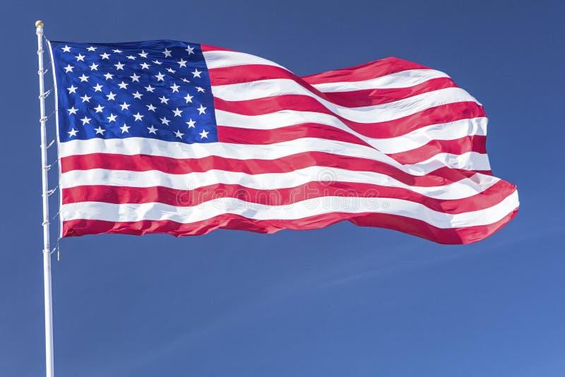 Stora flaggaamerikanUSA stjärnor gör randig blåsig blå himmel för polen royaltyfri fotografi