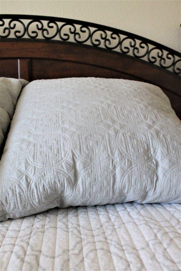 Stora Gray Pillow på en utgjord säng med en dekorativ huvudgavel royaltyfri foto