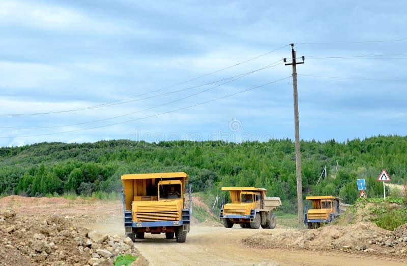 Stora gula dumper som arbetar i kalkstenöppen-gropen Päfyllning och trans. av mineraler i dolomiten som bryter villebrådet arkivbild