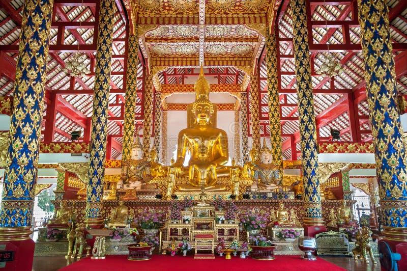 Stora guld- Buddhastatyer på altaret på Wat Suan Dok, Chiang Mai, Thailand arkivbilder