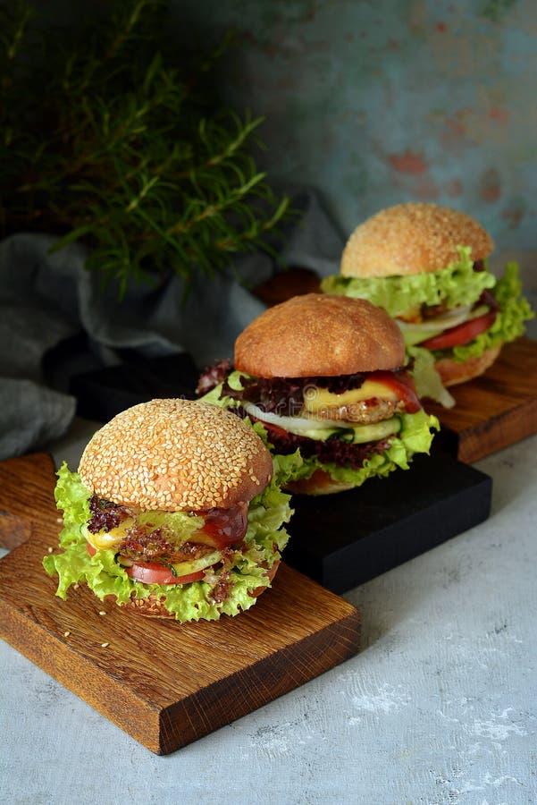 Stora hemlagade saftiga hamburgare för ett nötkött, grönsaker och en ny rulle Smörgås för frukostsnabbmat royaltyfri bild