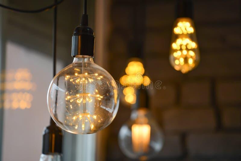 Stora idérika glödande ledde glödtrådmajskolvlampor, blured ljus på bakgrund, bokeh royaltyfri fotografi
