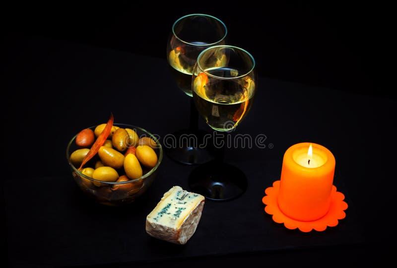 Stora inlagda gröna oliv, vitt vin, ädelost och stearinljus royaltyfri bild