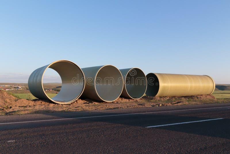 Stora konkreta rör som väntar på infrastrukturarbete arkivfoton