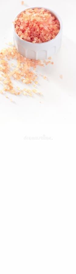Stora kristaller av rosa stora kristaller av rosa Himalayan saltar i krus Vit bakgrund Top beskådar Rengöringsdukbanerformat Hima arkivbild