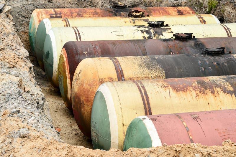Stora metallbehållare begravas i jordningen i produktionkriget arkivfoton