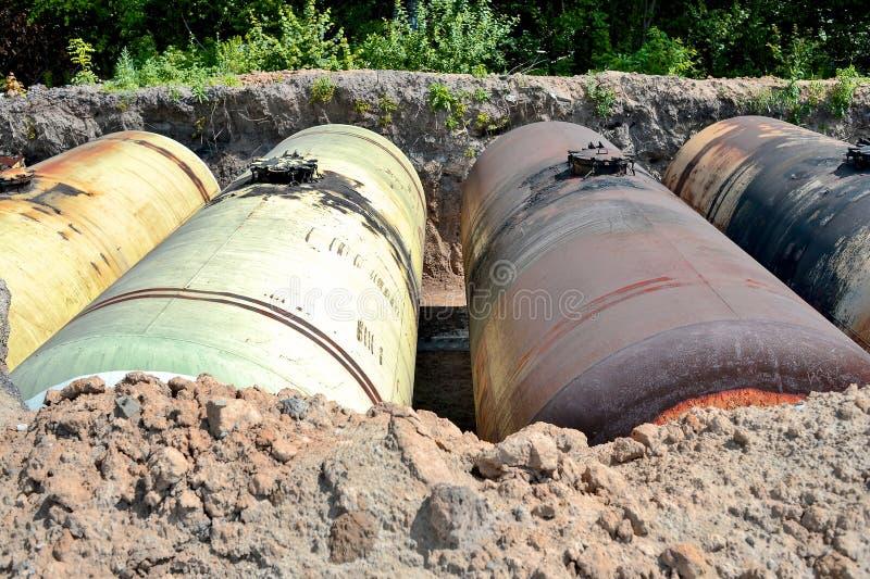 Stora metallbehållare begravas i jordningen i produktionlagret arkivbild