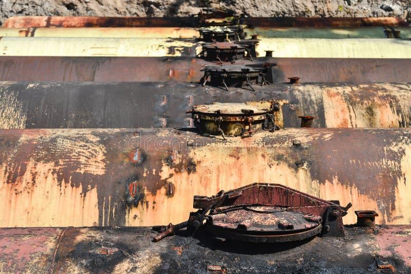 Stora metallbehållare begravas i jordningen i produktionlagret arkivbilder