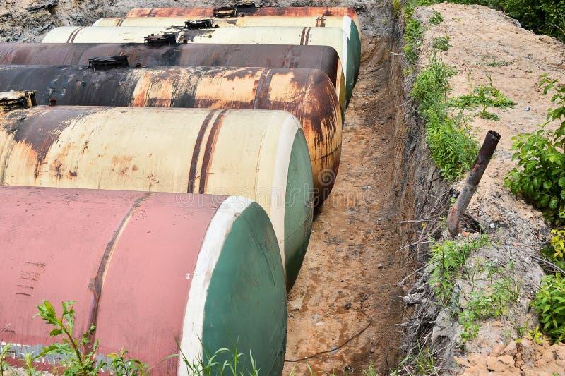 Stora metallbehållare begravas i jordningen i produktionlagret fotografering för bildbyråer