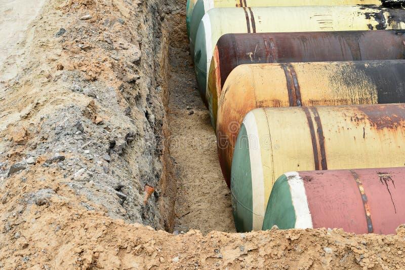 Stora metallbehållare begravas i jordningen i produktionlagret royaltyfri bild