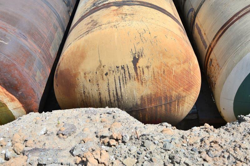 Stora metallbehållare begravas i jordningen i produktionlagret royaltyfri foto
