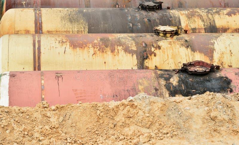 Stora metallbehållare begravas i jordningen i produktionlagret arkivfoto
