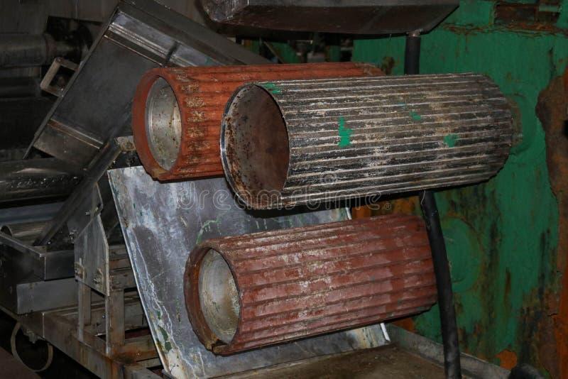 Stora metallrullrullar med t?nder av kugghjulen av produktionslinjen, en transportband i seminariet p? en industriell kemikalie royaltyfri foto